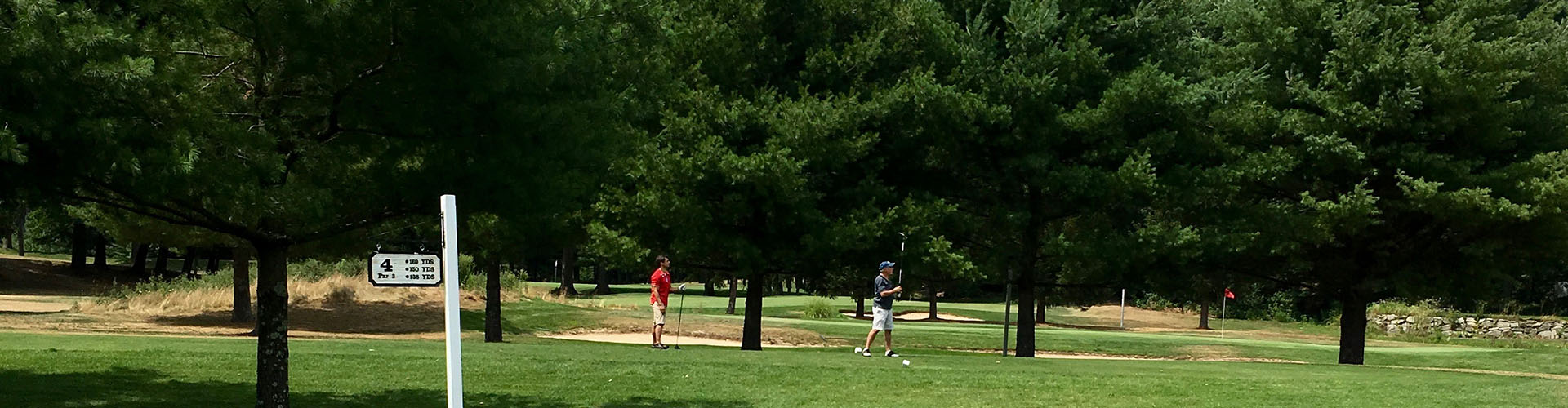 Golfers walk on the course at hole 4