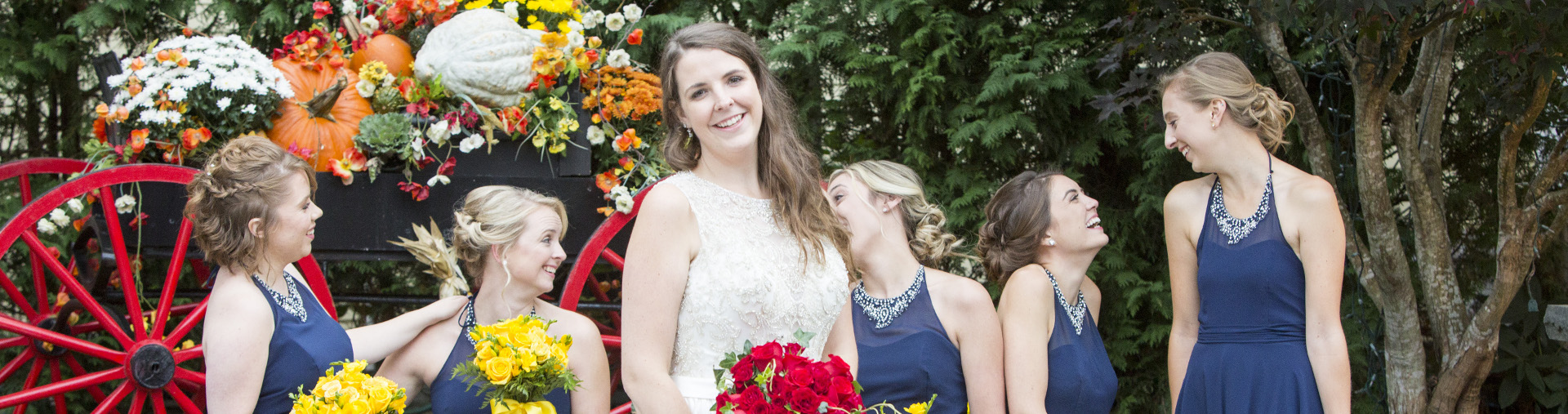 A bride poses with her bridesmaids on her wedding day at Butternut Farm