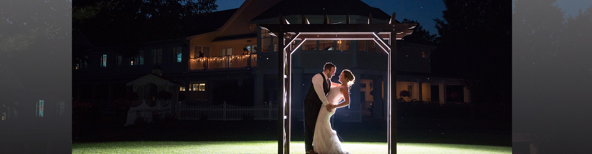 A newlywed couple poses for a picture in front of a clubhouse at Butternut Farm