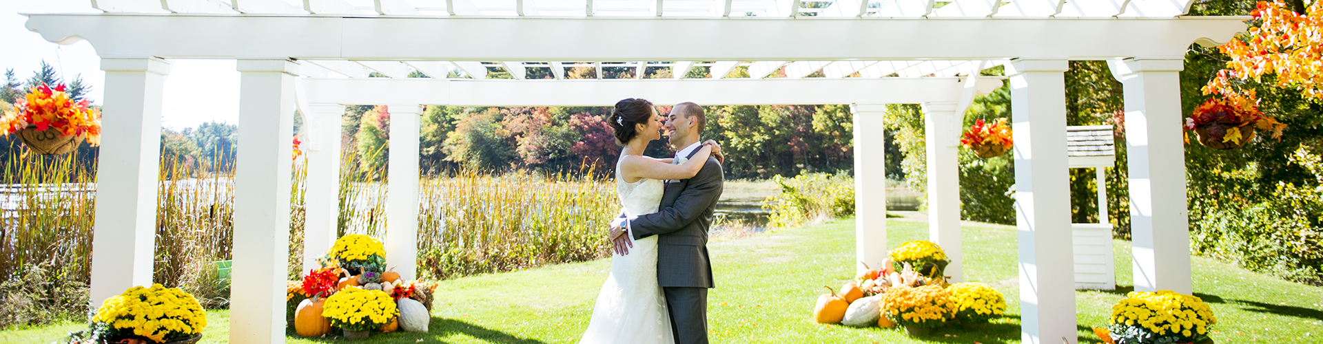 A newlywed couple embraces under a pergola at Butternut Farm